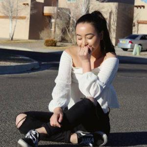 Mädchen sitzt auf Straße