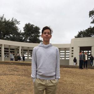 Junge steht mit Händen in den Hosentaschen auf Platz