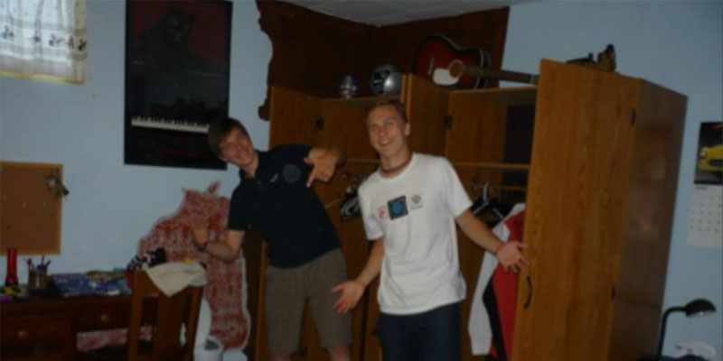 Zwei Jugendliche posieren gemeinsam in einem unaufgeräumten Zimmer