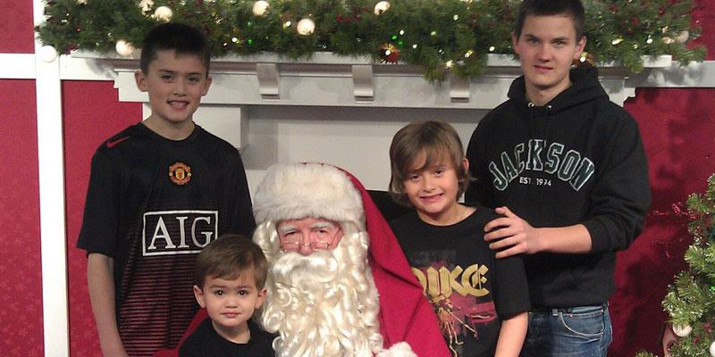4 Jungen unterschiedlichen Alters reihen sich um einen verkleideten Weihnachtsmann