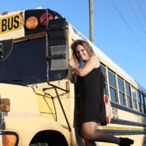 ein Mädchen vor einem amerikanischen Schulbus