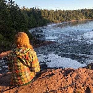 ein Mädchen sitzt auf einem Felsen am Meer