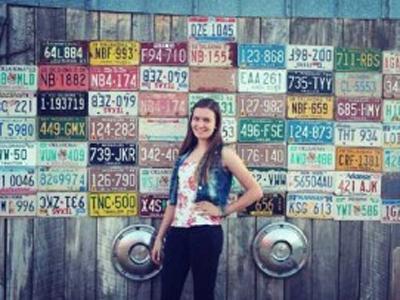 Caroline vor einer Wand mit Nummernschildern